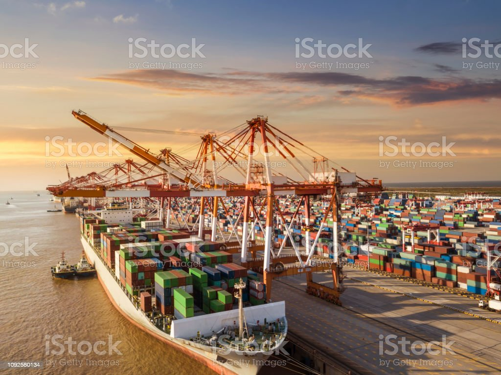 Container terminal handling area, aerial view Logistics and transportation of Container Cargo ship and Cargo plane with working crane bridge in shipyard, logistic import export and transport industry background Aerial View Stock Photo