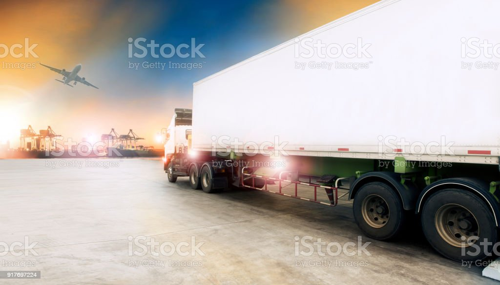 container truck in shipping port and cargo plane flying above stock photo