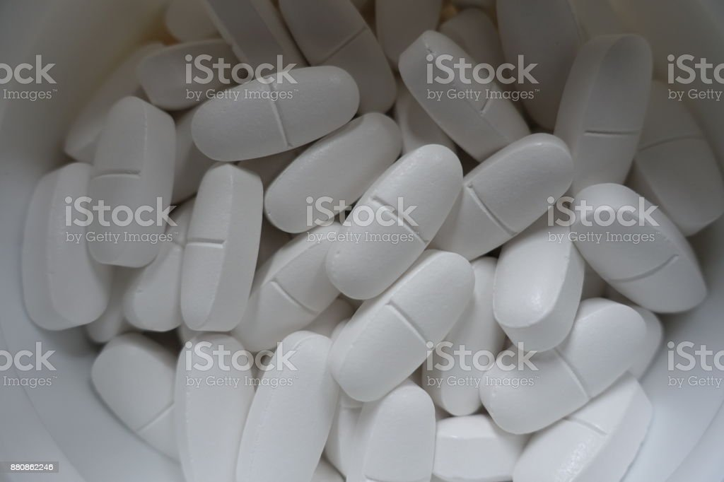 Container with big white calcium citrate tablets stock photo