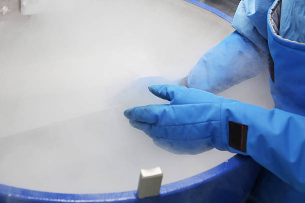 Container with liquid nitrogen...doctor in hazmat suit at work Doctor in hazmat suit working with container with embryonal cells in liquid nitrogen liquid nitrogen stock pictures, royalty-free photos & images