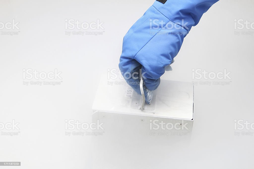 Container with liquid nitrogen...doctor in hazmat suit at work stock photo