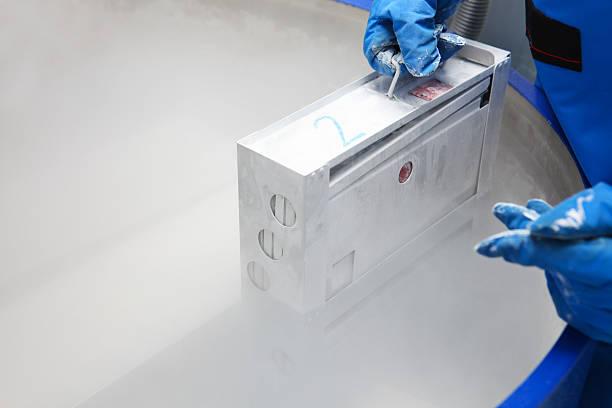 contenitore con il liquido nitrogen.doctor con tuta hazmat al lavoro - criobiologia foto e immagini stock