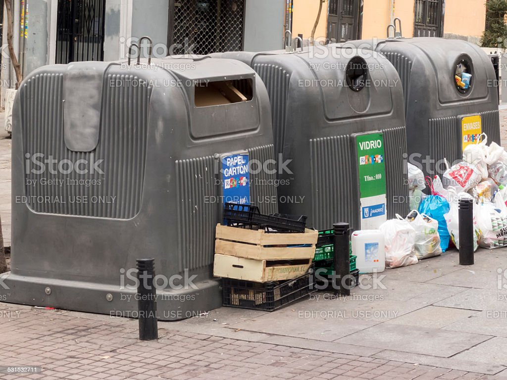 containers for recycling on the street surrounded by trash. stock photo