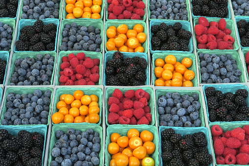 containers full of berries and little yellow tomatoes on display for sale at a farmer's market