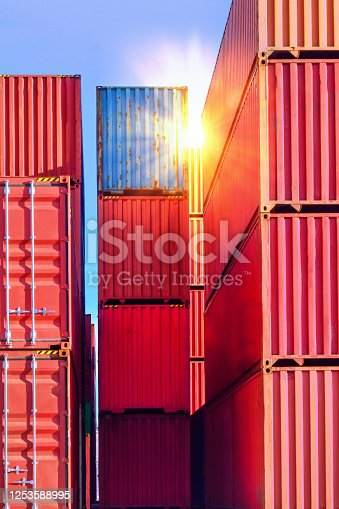 Containers stack inside container yardContainer handling. Container truck picking up container at yard. Port logistics, container yard operation. Container truck or Rubber Tired Gantry Cranes (RTG) picking up a container at yard. Port logistics, container yard operation.