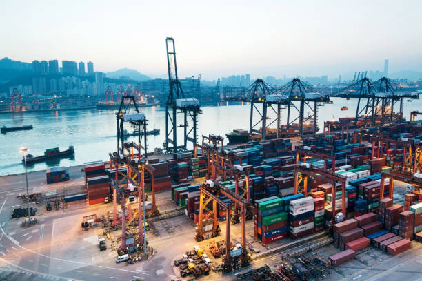 containers stacking in the harbor at dusk - scambio commerciale foto e immagini stock