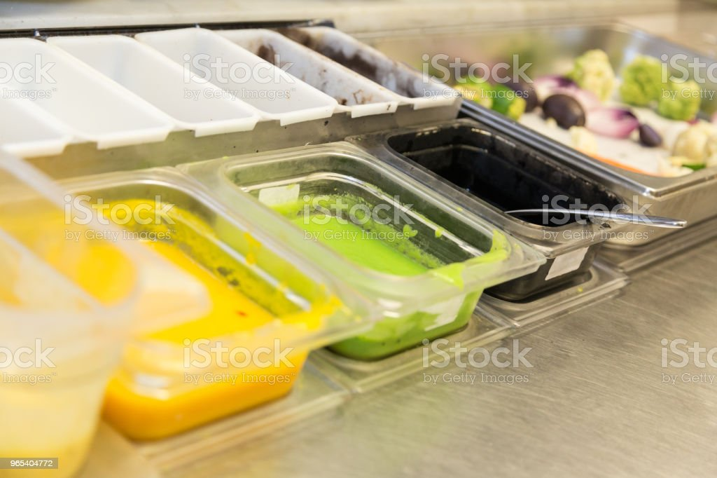 Containers with variety of sauces and a tray with vegetables on the kitchen counter zbiór zdjęć royalty-free