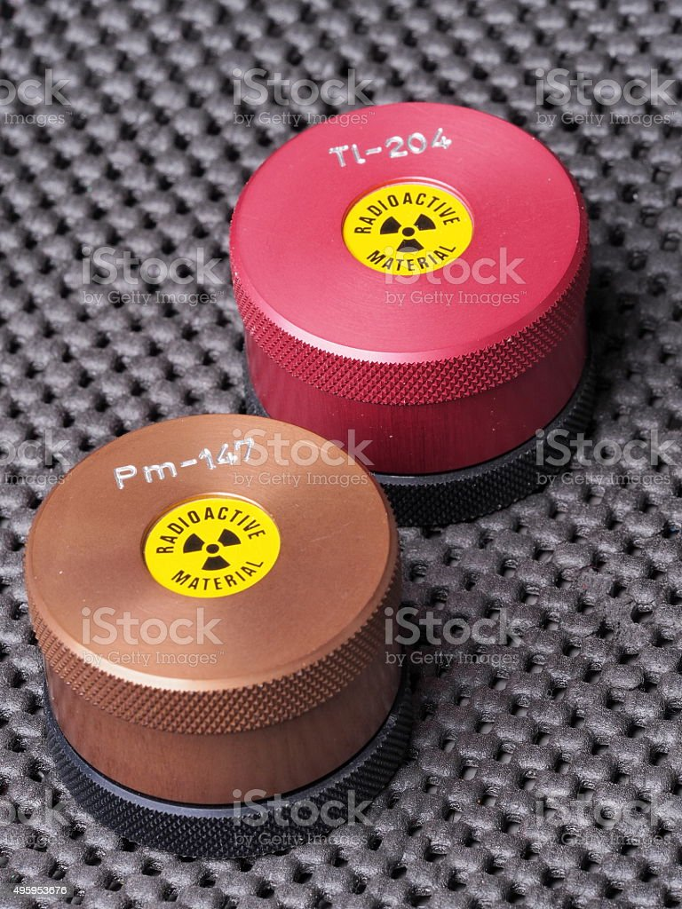 Containers with warning sticker containing radioactive isotopes Promethium and Thallium stock photo