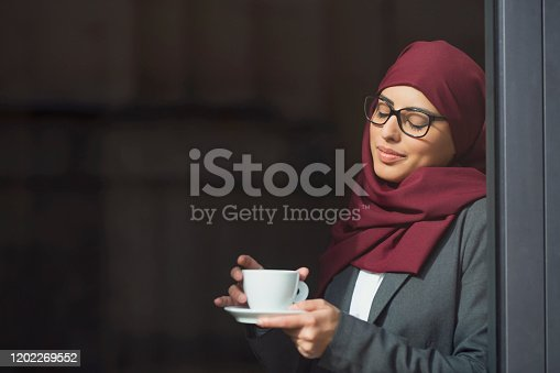 Arabian business woman with hijab enjoying her coffee.
