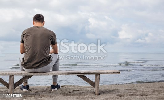 Contemplating man watching the waving sea from a beach while sitting on a bench.