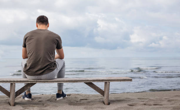 Betrachtendes Man watching the sea from a beach bench – Foto