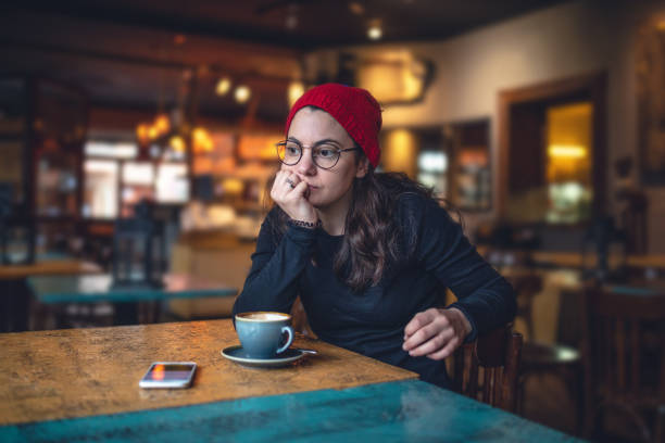 Contemplating student sitting at a coffee shop stock photo