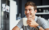 Shot of a happy young man enjoying a cup of coffee in his kitchen at home