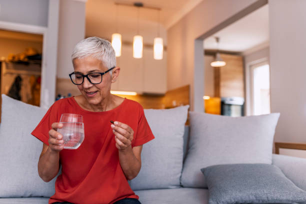 Contemplating the side-effects Photo of senior woman with glass of water taking pill at home. Age, medicine, healthcare and people concept. Mature woman taking pill against headaches at home. Woman taking medication for her illness. Gray hair woman at home taking pill to ease headache. woman taking pills stock pictures, royalty-free photos & images