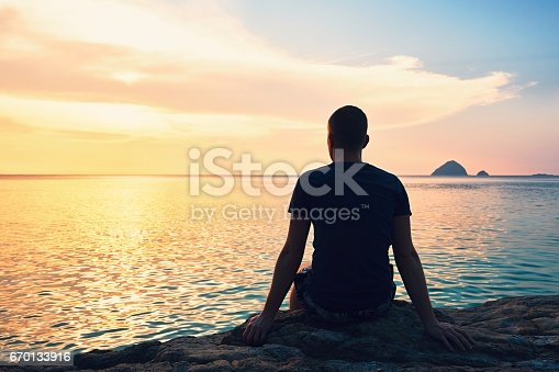 Contemplation at the beautiful sunset. Silhouette of the young man on the beach.