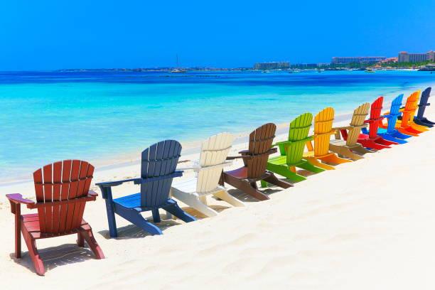 contemplatie: strand met kleurrijke buiten adirondack stoelen - aruba, caribische zee - aruba stockfoto's en -beelden