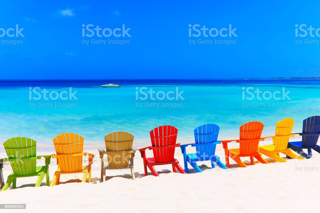 Contemplation: Tropical Beach with colorful adirondack chairs and speedboat -  Caribbean sea stock photo