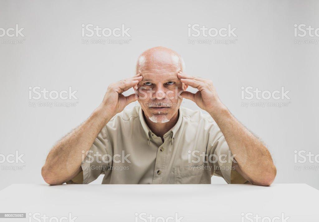 Contemplative balding man sitting at table stock photo