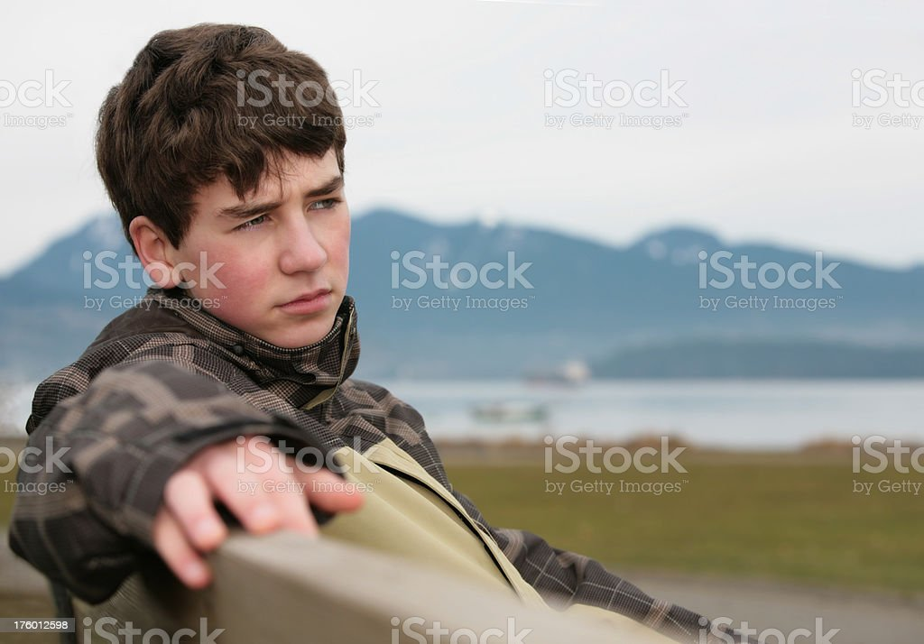 Contemplative Boy on Beach Bench royalty-free stock photo
