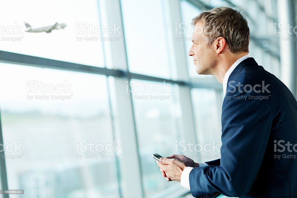 Contemplative Businessman Looking At An Airplane Taking Off. stock photo