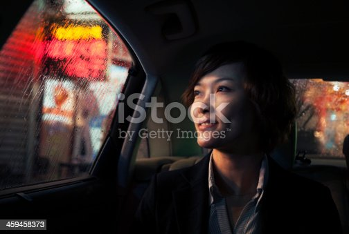 istock Contemplative Businesswoman looking out of car window through the rain 459458373
