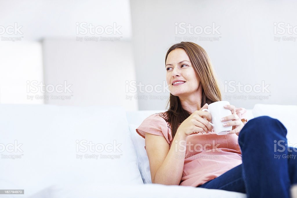 Contemplative lady holding a coffee cup while sitting on couch royalty-free stock photo