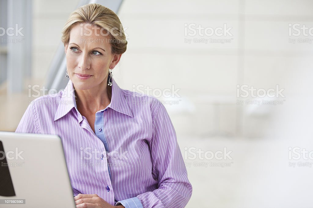 Contemplative mature businesswoman working on laptop at office royalty-free stock photo