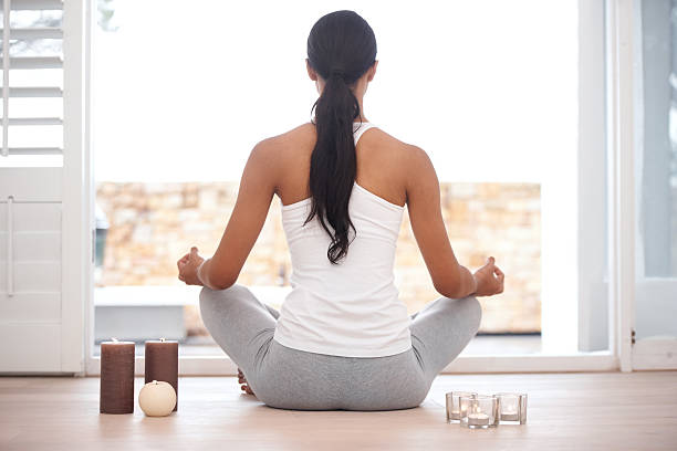 Contemplative meditation Rearview image of a woman meditating at home lotus position stock pictures, royalty-free photos & images