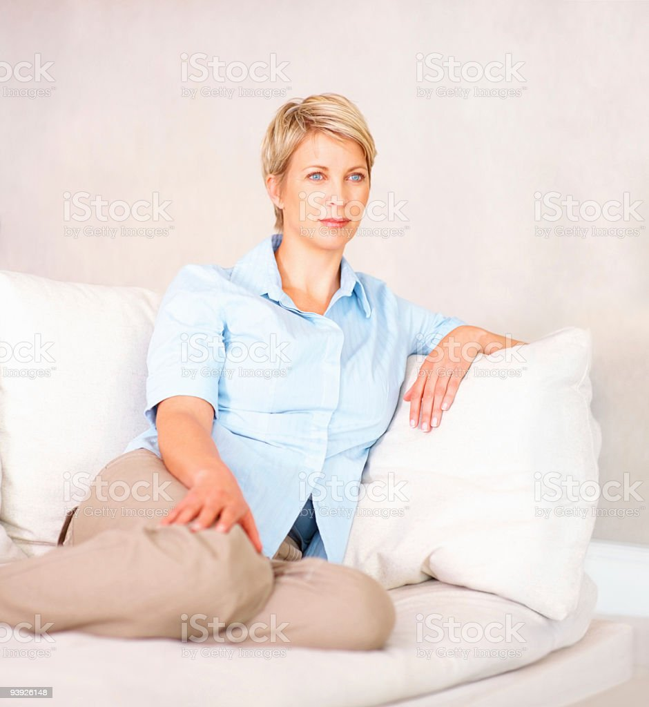 Contemplative mid aged lady sitting on couch royalty-free stock photo