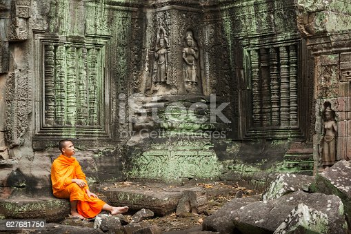 Contemplative Cambodian monk in an orange robe sits on the ancient steps of a temple ruin lost in thought looking at ancient carvings, Siem Reap, Cambodia, Asia