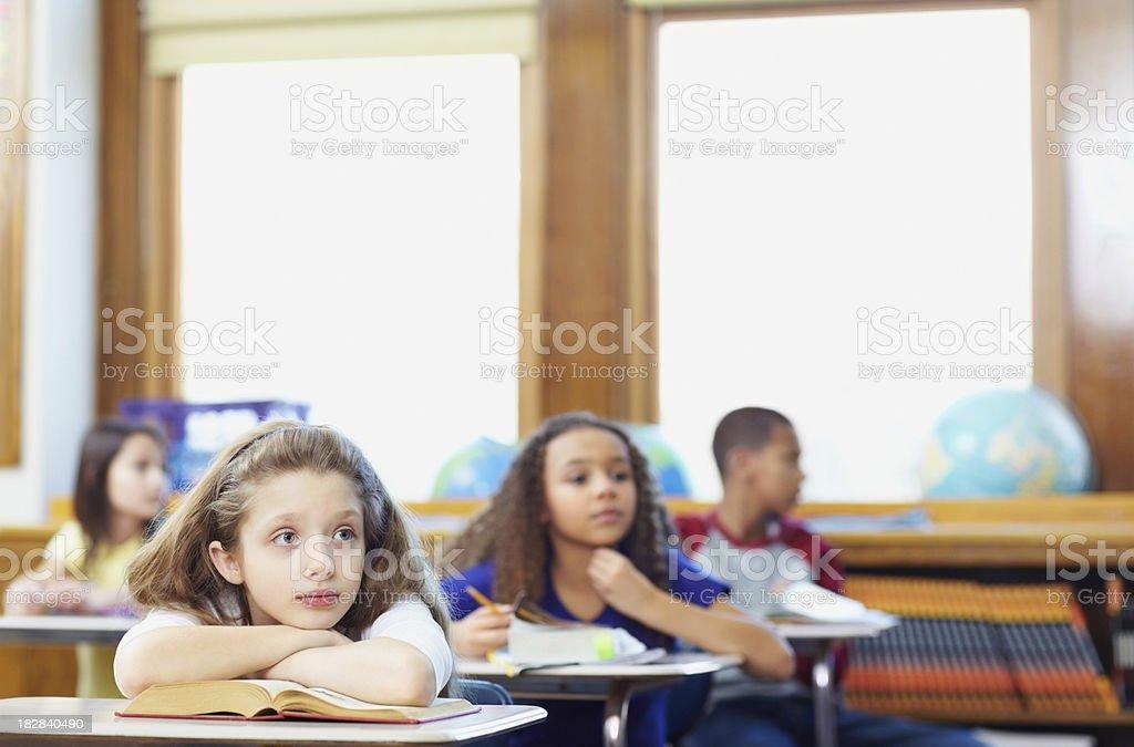 Contemplative school children sitting in classroom stock photo