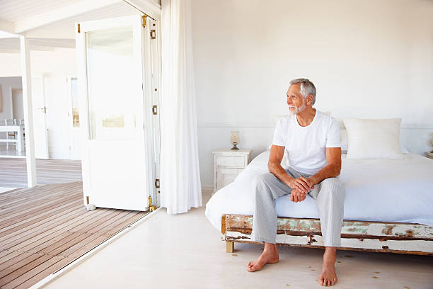 Contemplative senior man sitting on bed Contemplative senior man sitting on bed 65 69 years stock pictures, royalty-free photos & images