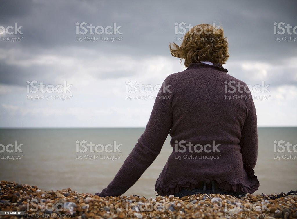 Contemplative woman sits at pebbly beach royalty-free stock photo