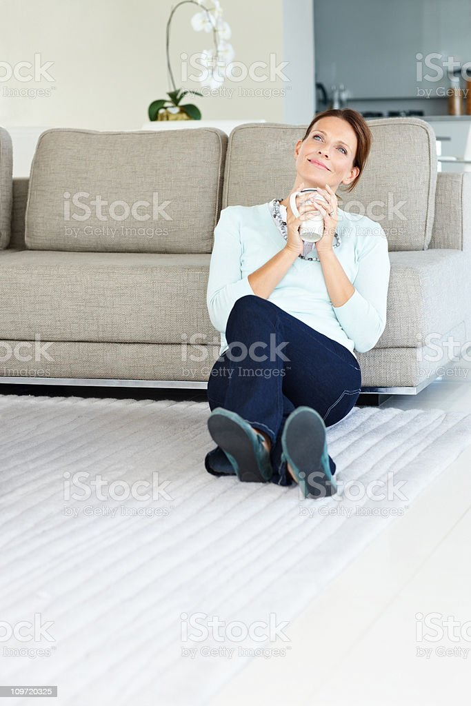 Contemplative woman with a coffee cup sitting on floor royalty-free stock photo