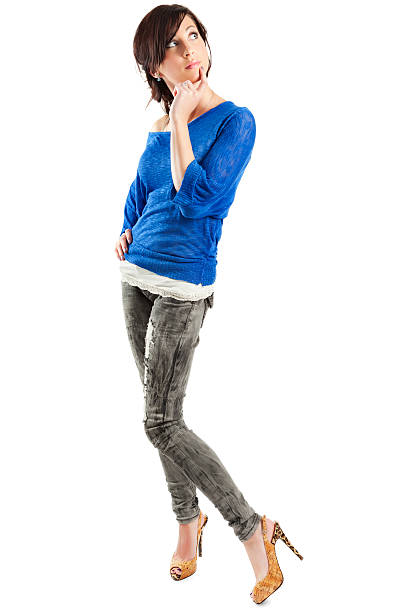 """Contemplative Young Woman on White """"Photo of an attractive young woman in blue sweater and jeans, standing with a contemplative expression on her face; isolated on white."""" skinny jeans stock pictures, royalty-free photos & images"""