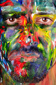 Close up shot of a man who has a painted face.