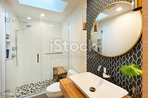 A contemporary modern bathroom design. featuring  a round mirror, an above counter vessel sink, custom built vanity with storage, toilet and walk-in glass shower stall.