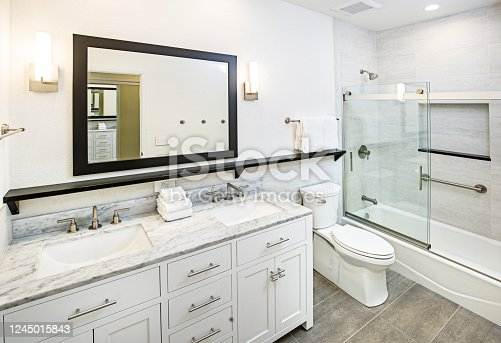 A contemporary modern bathroom design. featuring a bathtub with glass shower stall, toilet and his and her double sink vanity.