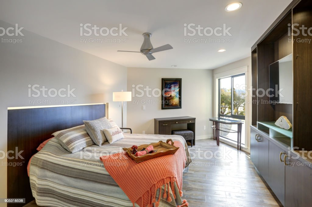 Contemporary condo home bedroom interior features a nice bed with lit...