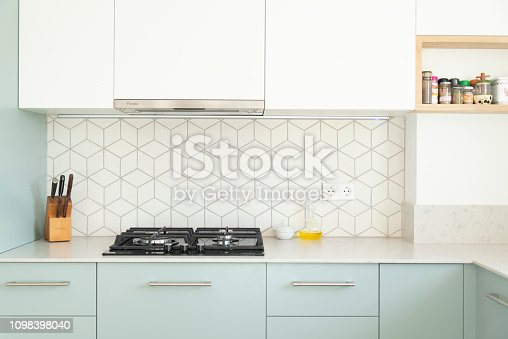 Scandinavian style kitchen with geometric backsplash and blue and white cupboards