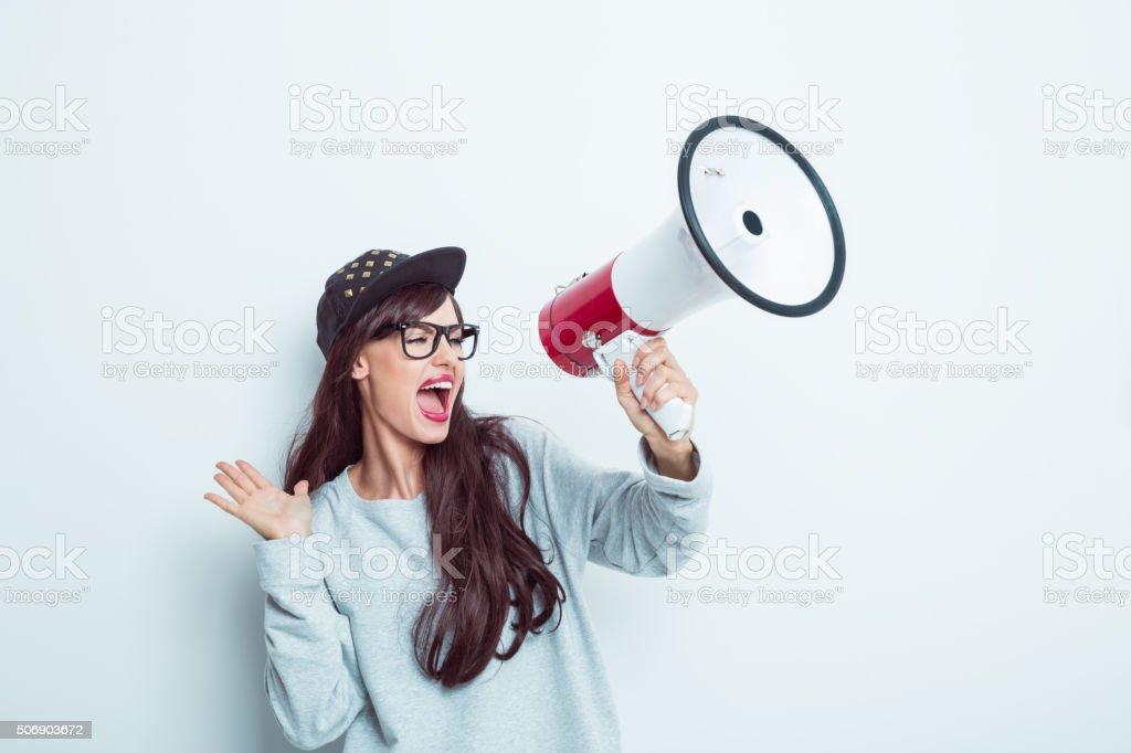 Contemporary girl shouting into megaphone stock photo