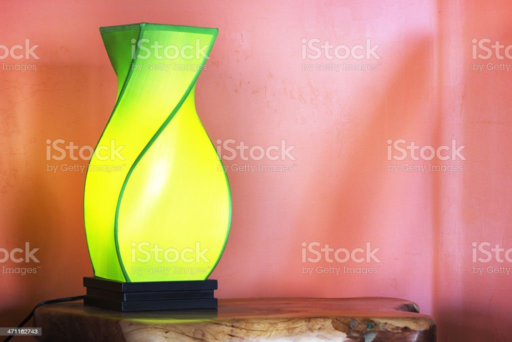 Contemporary green and yellow lampshade over a pink wall royalty-free stock photo