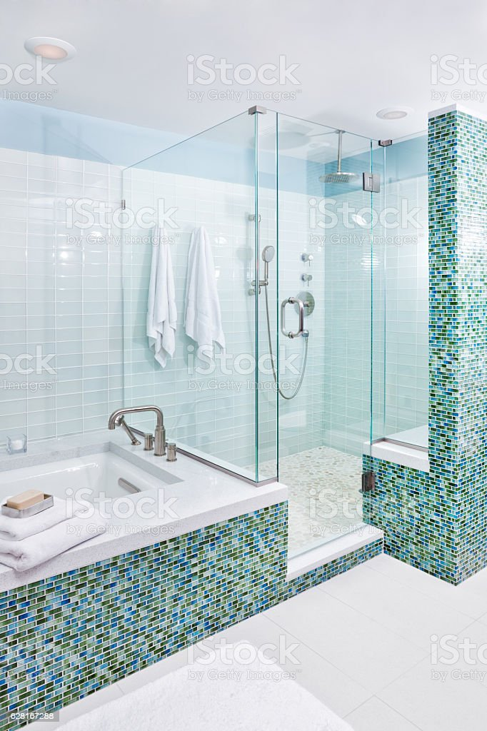 Contemporary Home Bathroom with Shower Stall, Tub and Glass Tiles stock photo