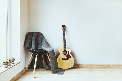 istock Contemporary home interior. Black chair covered with woolen gray blanket and acoustic guitar in front of an empty white wall. Succulent plants on the window. 1150856266