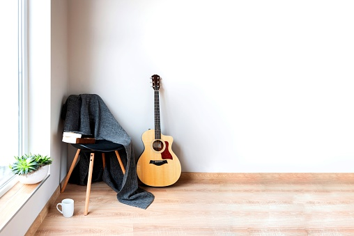 istock Contemporary home interior. Black chair covered with woolen gray blanket and acoustic guitar in front of an empty white wall. Succulent plants on the window. 1187532845