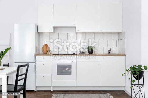 Contemporary kitchen with white cupboards and dining table with black chairs