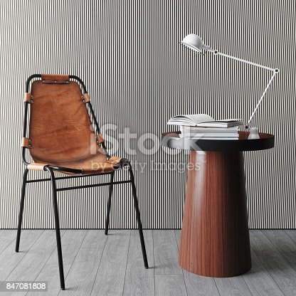 Interior of a living room with modern chair, side table, lamp and books.