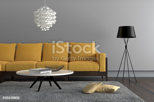 Close up of a living room showing a yellow sofa, with a lamp, ornate pendant and a table with decoration. There is a gray carpet with two pillows on it. Gray wall surrounding the scene with wooden floor.