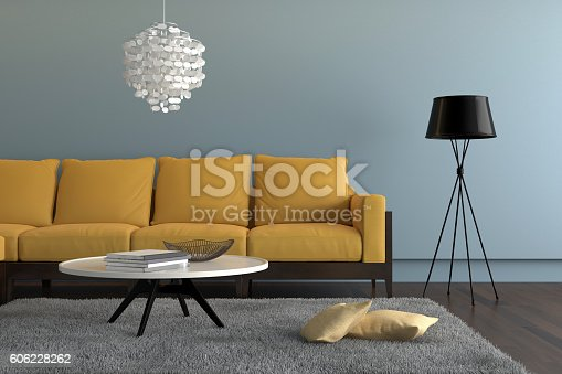 Close up view of a living room showing a yellow orange sofa, with a lamp, ornate pendant and a table with decoration. There is a gray carpet with two pillows on it. Light blue wall surrounding the scene with wooden floor. Horizontal composition.