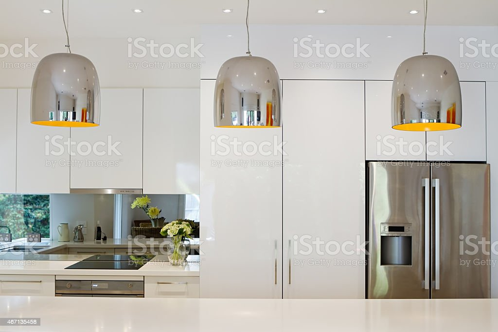 Contemporary pendant lights hanging over kitchen island stock photo